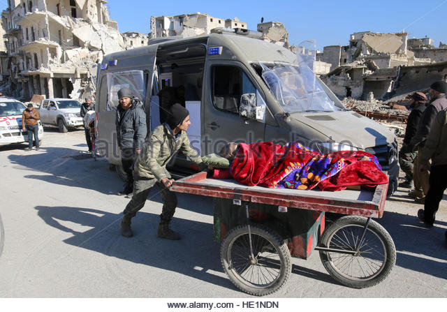 A man pushes a cart with a woman lying on it as vehicles wait to evacuate people from a rebel-held sector of eastern - Stock-Bilder