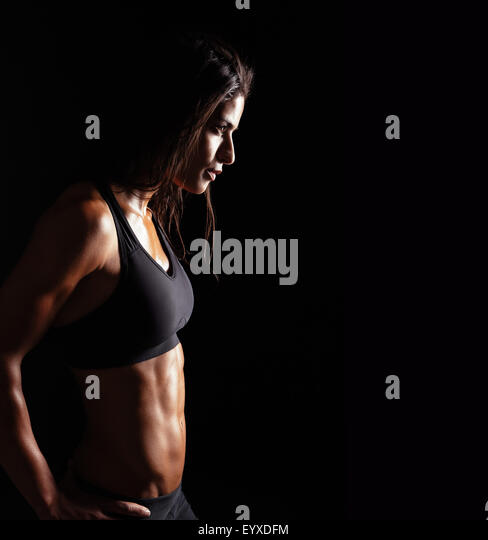 Image of fitness woman in sports clothing looking away on black background. Young female with perfect muscular body. - Stock-Bilder