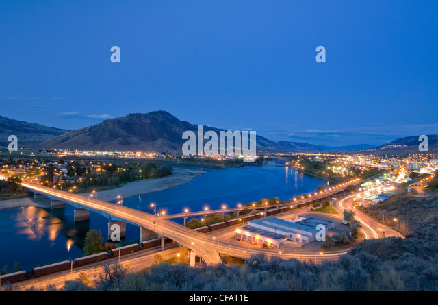 Sage brush creates the foreground for a dynamic dusk scene over Kamloops, British Columbia, Canada - Stock Image