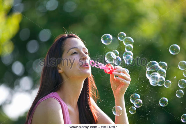 Carefree happy woman blowing bubbles with bubble wand - Stock-Bilder