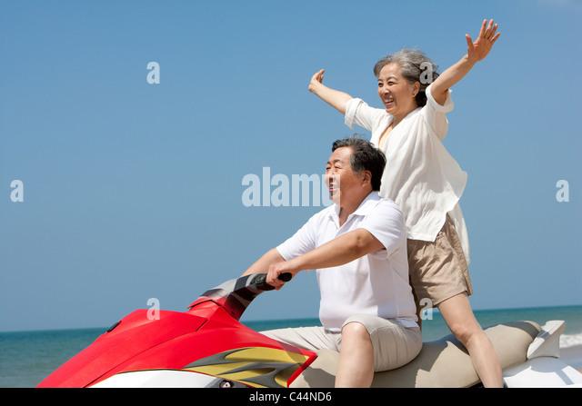 Happy Senior Couple Jet Skiing - Stock Image