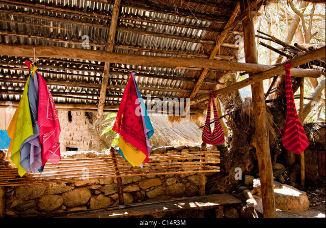 Hand made handkerchiefs and bags hang on wooden trusses beneath a gazebo on the Inca Trail. - Stock Image