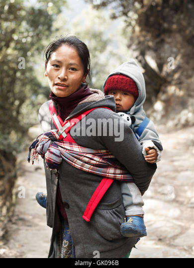 A mother with her child journeying through the mountains near Lukla, Nepal - Stock Image