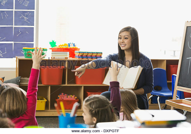 Teacher pointing at student with hands raised in class - Stock Image