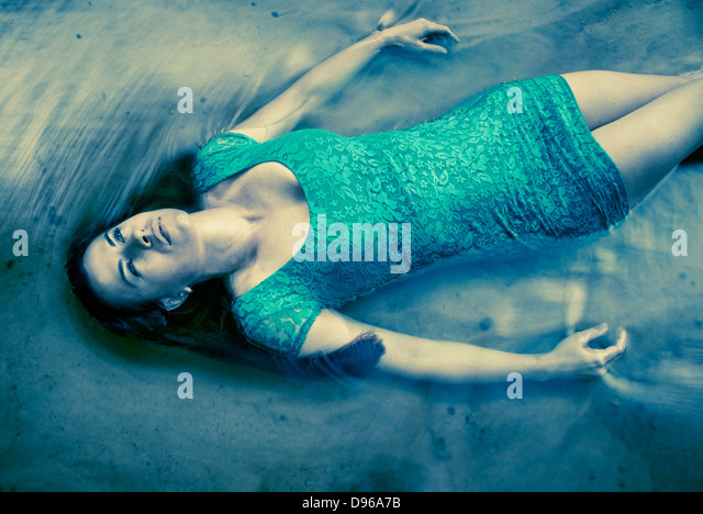 Woman in blue dress floating in water - Stock Image