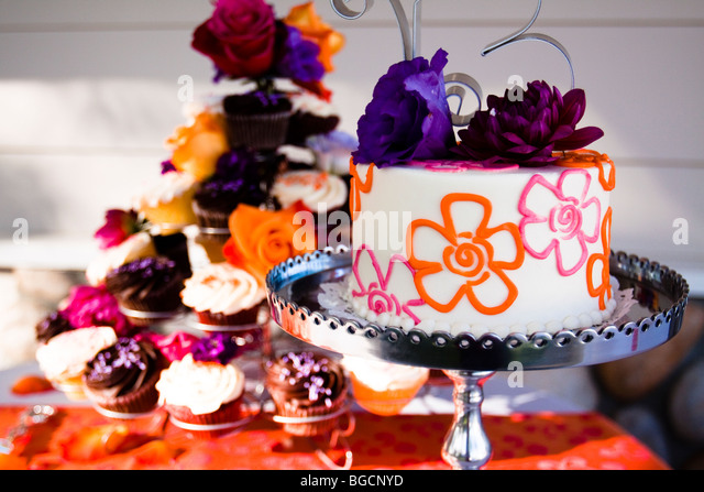 Decorated wedding cake on silver tray with cupcakes - Stock Image