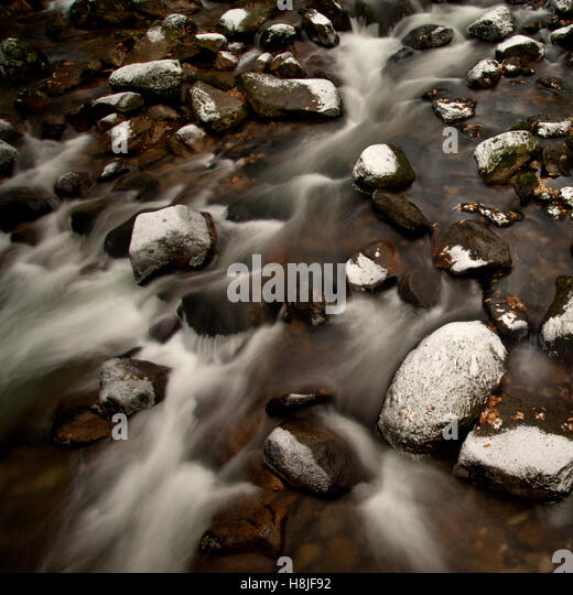 River Plym on Dartmoor National Park during winter with snow covered boulders and icy water. - Stock Image
