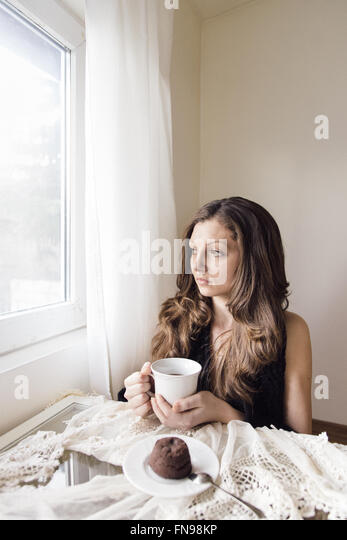 Young woman sitting with cup of tea and chocolate dessert - Stock-Bilder