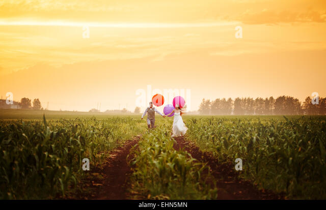 Happy young wedding couple running on the sunset field with big bright colorful balloons - Stock-Bilder