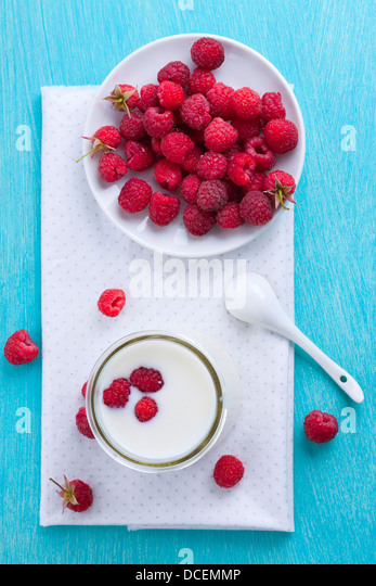 Glass of milk and some raspberries on plate shot from above - Stock Image
