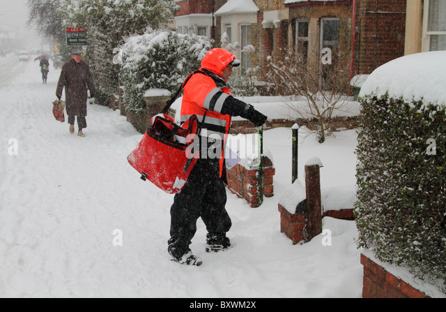 Christmas post postman snow delivery winter - Stock Image