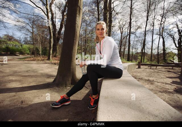 Female runner taking a rest from training in nature. Attractive young woman sitting relaxed with a water bottle. - Stock Image