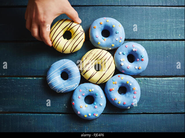 Close-up of male hand grabbing delicious donut - Stock Image
