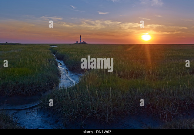 Sunset at the lighthouse Westerheversand, Eiderstedt peninsula, North Frisia, Schleswig-Holstein, Germany - Stock Image