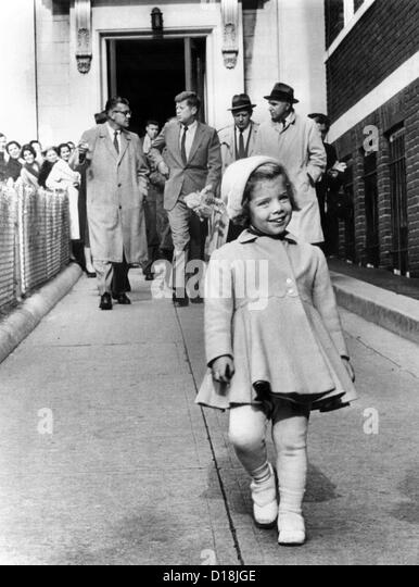 Caroline Kennedy on her third birthday. In the background, her father, President -elect John Kennedy holds her doll - Stock Image