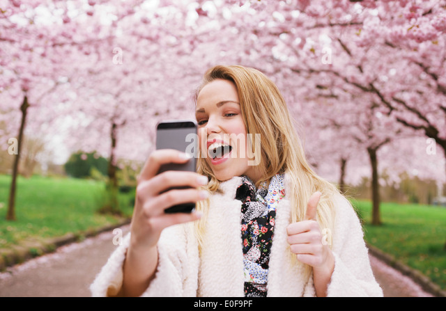 Cheerful young woman talking her picture with her cell phone and gesturing thumbs up sign. Caucasian female model - Stock Image