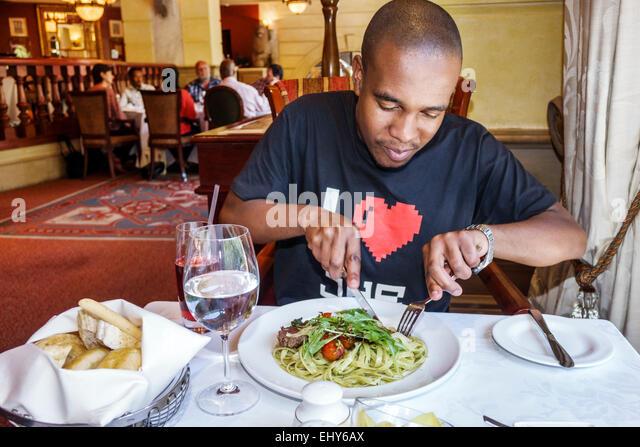 Johannesburg South Africa African Sandton Nelson Mandela Square Piccolo Mondo restaurant inside Black man lunch - Stock Image
