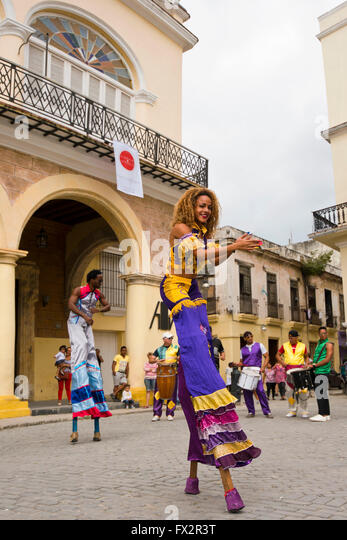 Vertical portrait of stilt walkers performing a dance routine in Havana, Cuba. - Stock Image