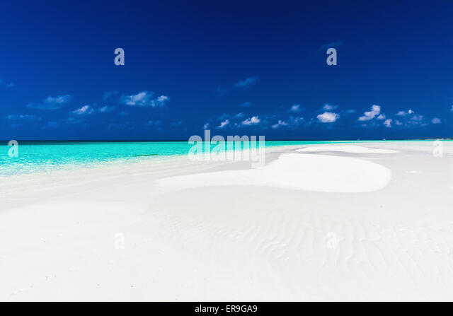 Small empty sandbar in the middle of tropical lagoon in atoll of Maldives - Stock Image