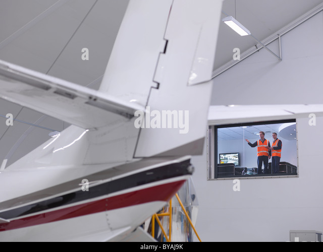 Engineers look out onto jet aircraft - Stock Image