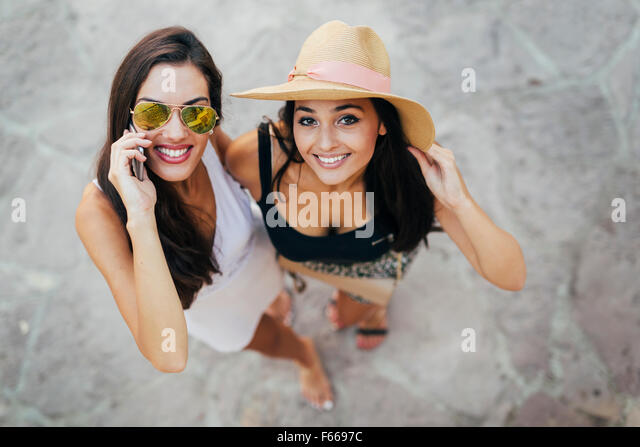Beautiful friends outdoor having fun and talking on phone - Stock Image