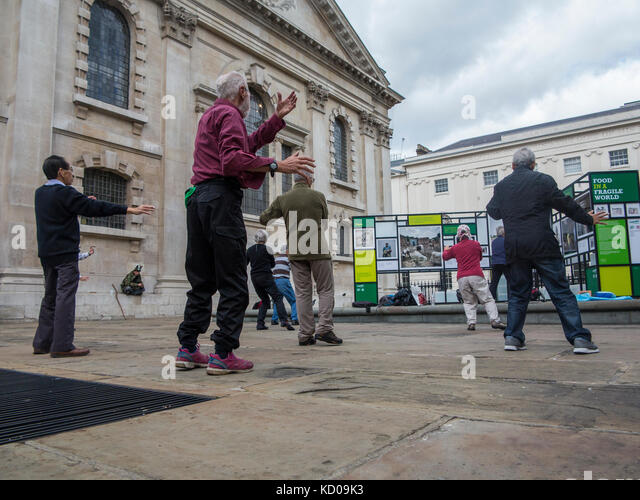 Tai chi class for more elderly people in St Martins in the Fields churchyard - Stock Image