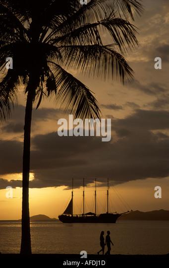 Venezuela Puerta la Cruz Caribbean Sea shore couple sunset masted sailing ship SV Fantome - Stock Image