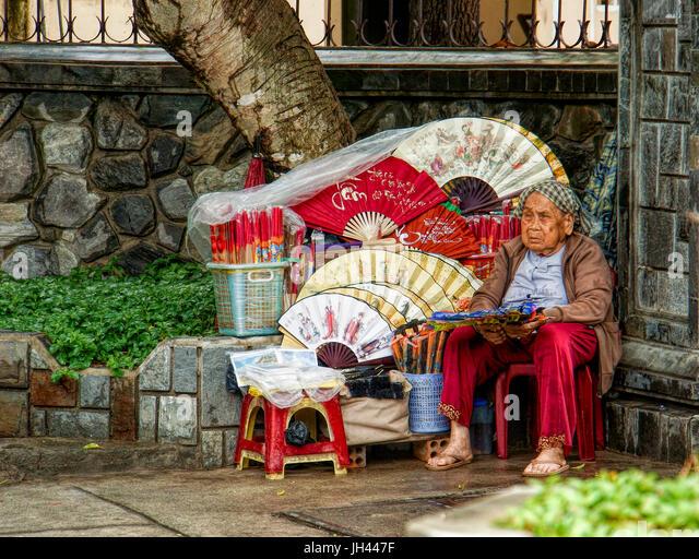 An older woman sells fans at a Temple. Nha Trang, Vietnam - Stock Image