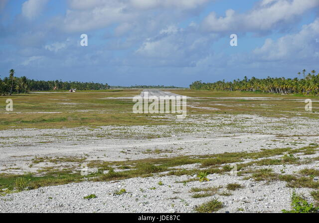 The airplane landing field on Tikehau atoll lined by coconut trees plantations, Tuamotus archipelago, French Polynesia, - Stock Image