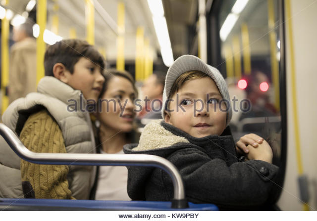 Cute boy riding bus with mother and brother - Stock Image