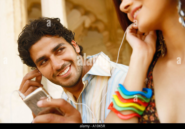 Close-up of a young couple listening to music on headphones, Agra Fort, Agra, Uttar Pradesh, India - Stock-Bilder