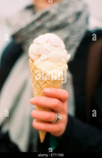 A woman holding out an icecream in a cone and laughing. - Stock Image
