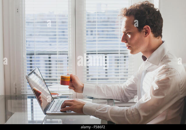 businessman reading emails in the office with cup of coffee - Stock Image