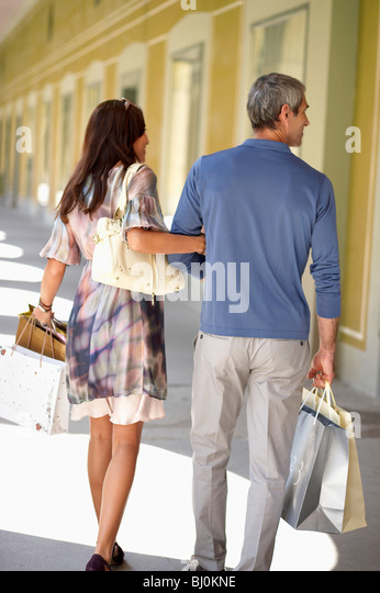 rear view of couple carrying shopping bags - Stock Image