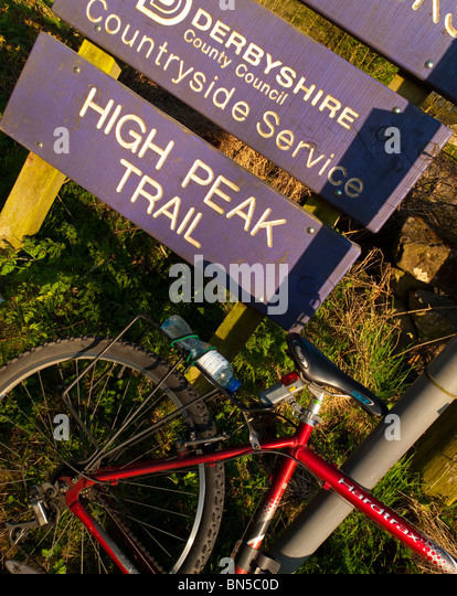 Cycle parked next to sign on the High Peak Trail near Wirksworth in the Derbyshire Dales part of the Peak District - Stock Image