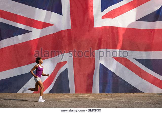 Woman running past british flag - Stock Image