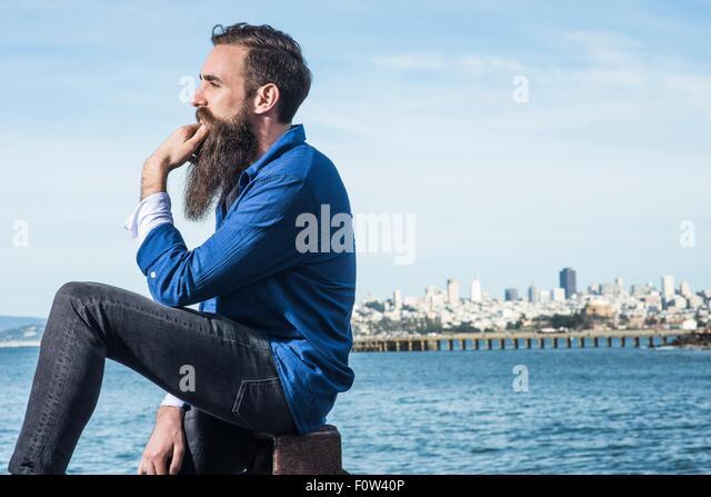 Man with beard sitting at Port Point, San Francisco, California, USA - Stock-Bilder