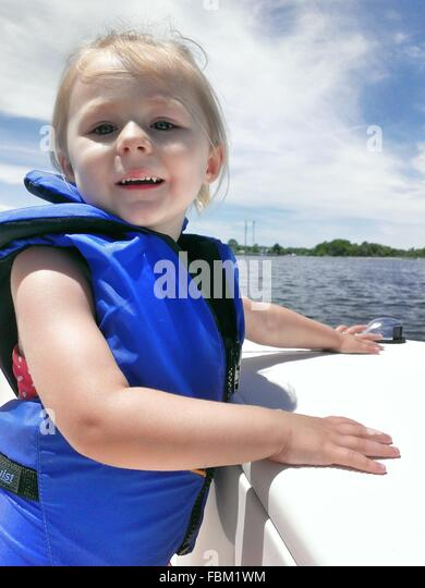 Portrait Of Cheerful Girl In Safety Jacket - Stock Image