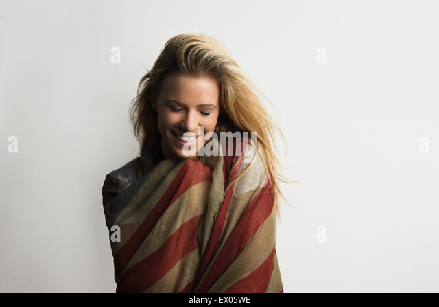Studio portrait of shy young woman wrapped in American flag - Stock Image
