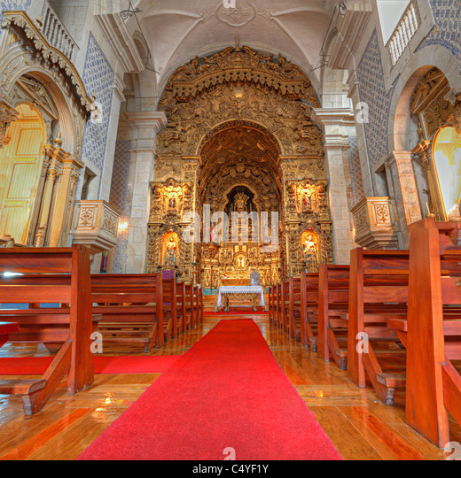 portuguese catholic church with wooden benches azulejos tile interior, lavish golden altar and red carpet, Porto, - Stock Image