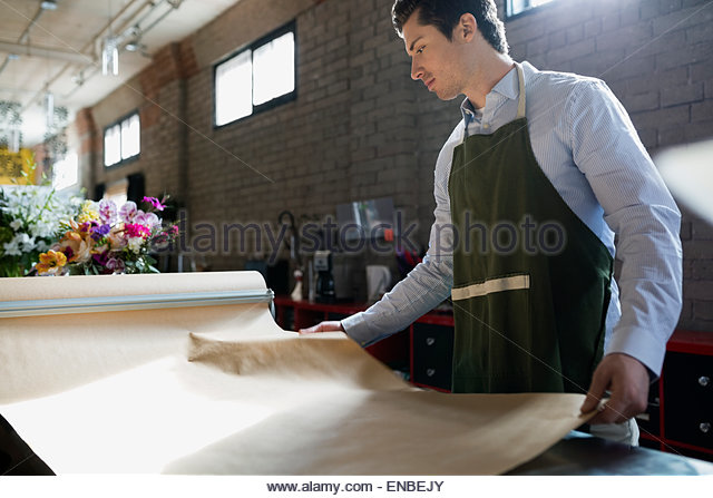Florist arranging craft paper in flower shop - Stock Image