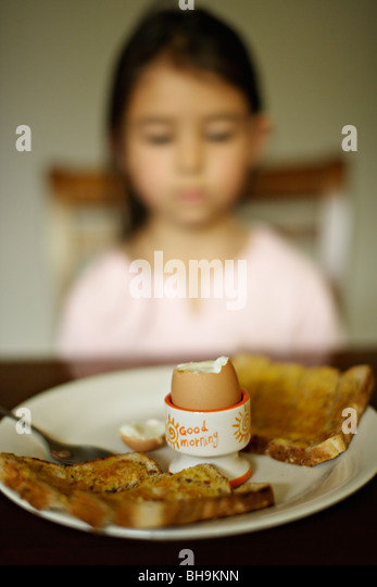 Six year old girl has boiled egg for breakfast - Stock Image