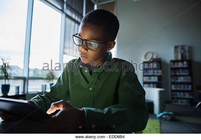 Elementary student using digital tablet in dark library - Stock Image