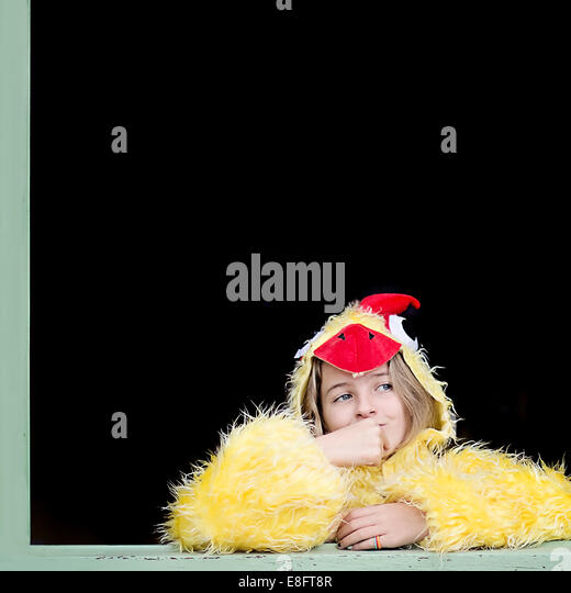 Girl dressed in a chick costume looking out of a window - Stock Image