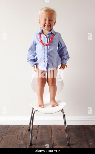 Little boy in blue dress shirt standing on chair - Stock Image