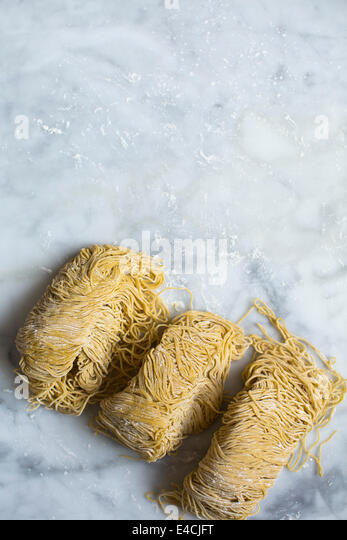 Fresh egg noodles and flour on marble background - Stock Image