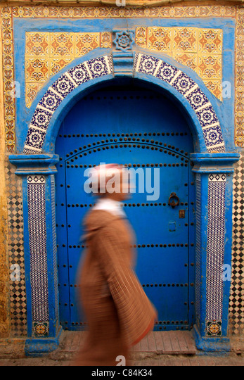 Young woman wearing a jellabah walks past a decorative wooden & tiled door in the medina/old walled town, Essaouira, - Stock-Bilder
