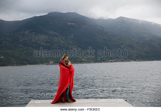 Romantic couple wrapped in blanket on lake dock - Stock-Bilder
