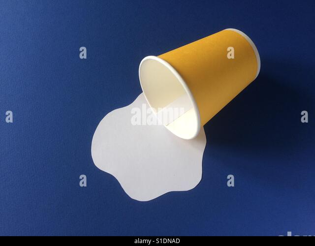 Milk spilled from yellow disposable cup on blue background. Paper craft concept. - Stock Image