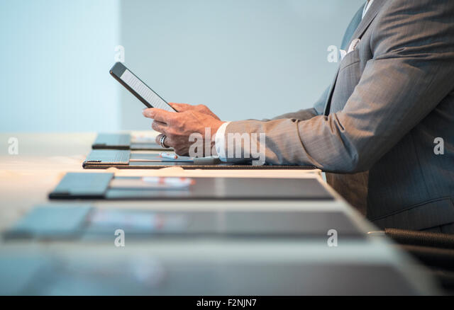 Caucasian businessman using digital tablet at conference table - Stock Image